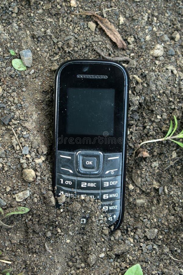 Un teléfono viejo enterrado en la tierra foto de archivo libre de regalías