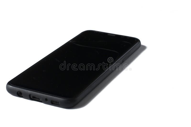 Un tel?fono negro con una pantalla agrietada aislada en un fondo blanco imágenes de archivo libres de regalías