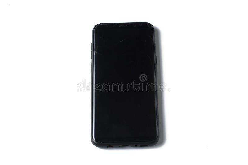 Un tel?fono negro con una pantalla agrietada aislada en un fondo blanco fotografía de archivo