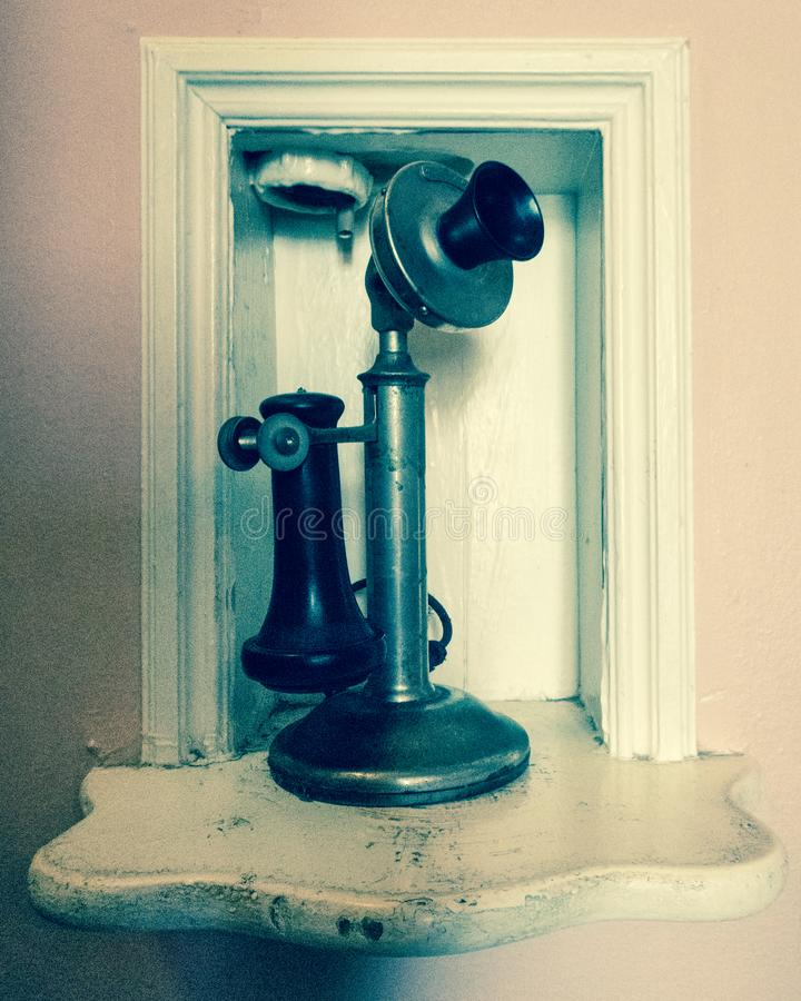 Un telefono antiquato appollaiato su uno scaffale fotografia stock