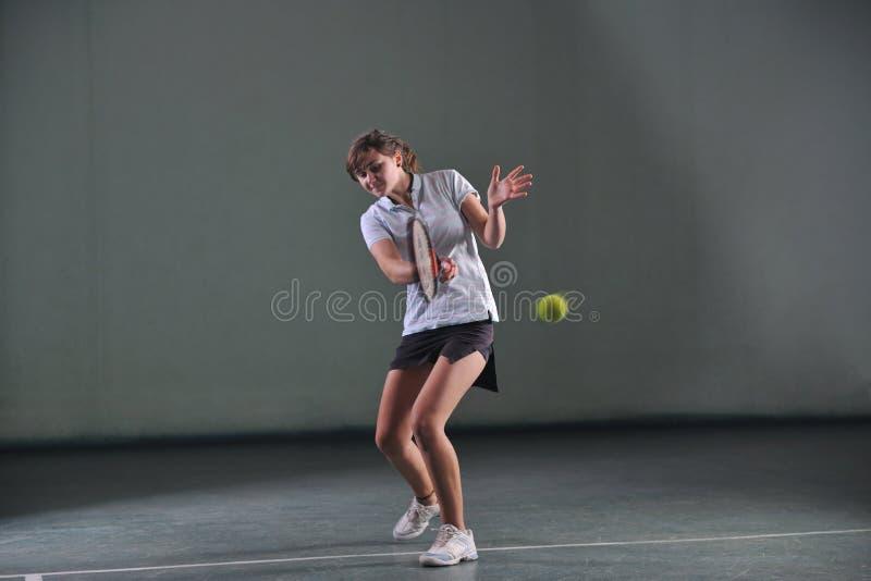 Un tennis del gioco della giovane donna fotografia stock