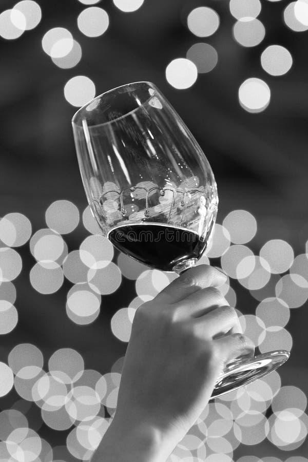 Un tenuto in mano un vetro di vino ad un partito, fondo con le luci vaghe fotografia stock
