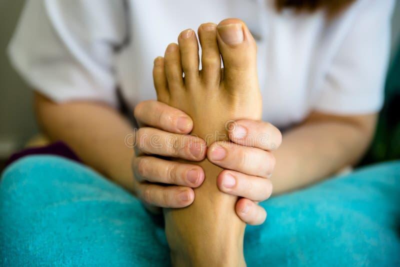 Un terapeuta de la hembra da masajes a pies del ` un s del paciente fotos de archivo libres de regalías