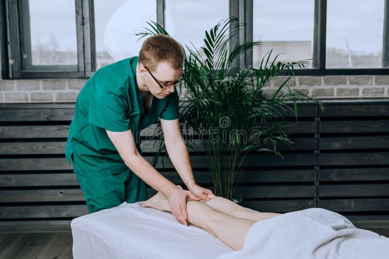 Un terapeuta de sexo masculino del masaje da masajes a los pies y a las piernas de piernas femeninas Masaje del becerro del pie imagen de archivo
