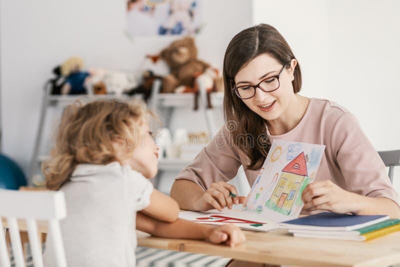Un terapeuta profesional de la educación del niño que tiene una reunión con un niño en un centro de ayuda de la familia imagen de archivo libre de regalías