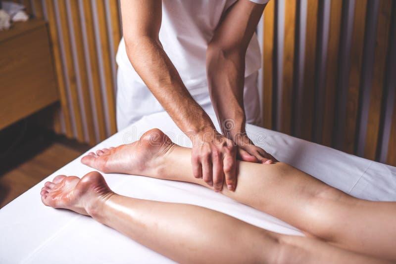 Un terapista di massaggio del maschio massaggia le gambe femminili nel salone di massaggio immagine stock libera da diritti