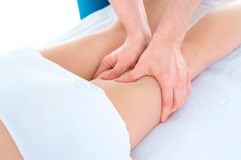 Un terapista di massaggio del maschio massaggia le gambe femminili nel salone di massaggio Le mani del massaggiatore fanno un mas fotografie stock libere da diritti
