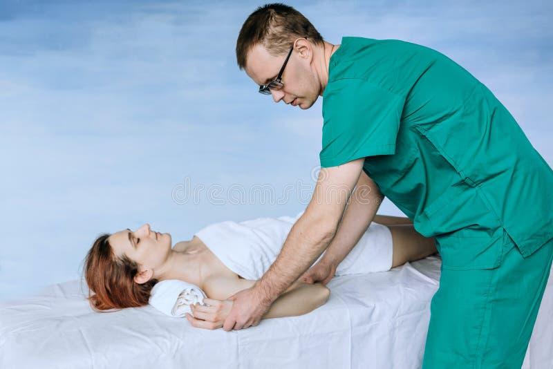 Un terapista maschio di massaggio che fa un massaggio del gomito ad una ragazza fotografia stock libera da diritti