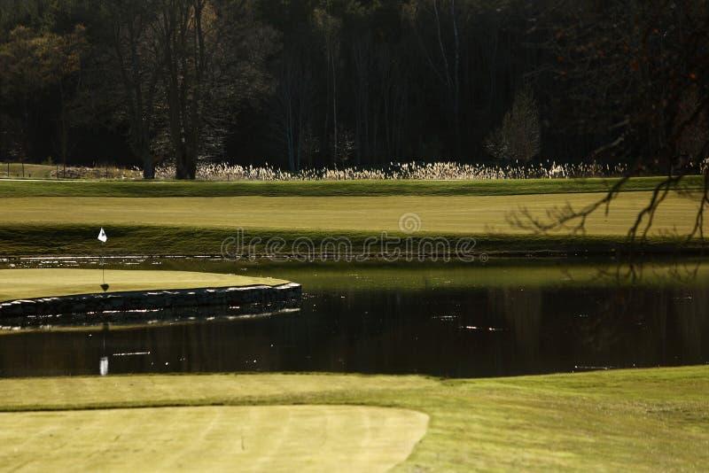 Un terrain de golf avec des routes, des soutes et des étangs et avec le drapeau images stock
