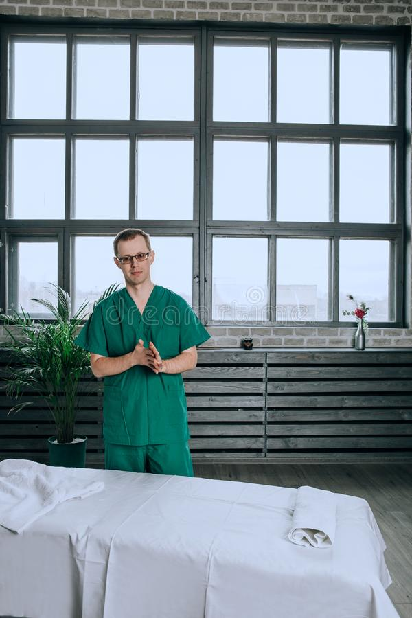 Un thérapeute masculin de massage dans un costume vert est souriant et étant prêt pour le travail photos stock
