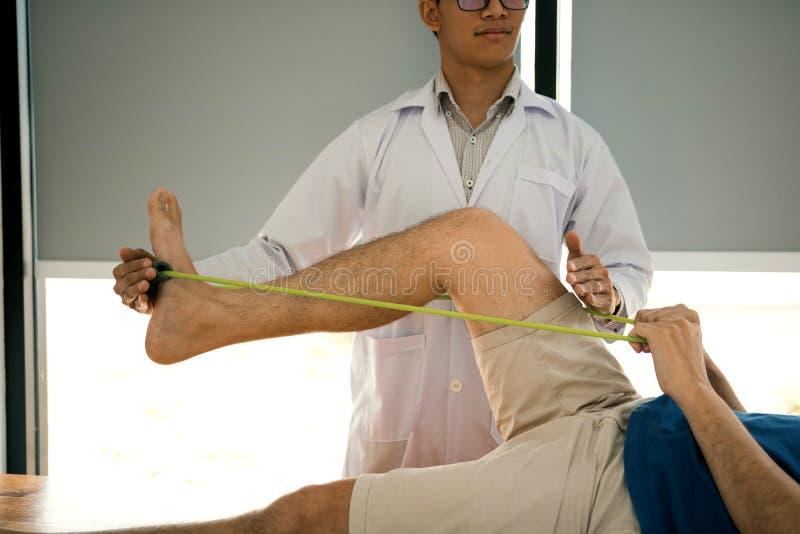 Un thérapeute physique confiant aide le patient à utiliser une bande de résistance qui s'étire la jambe dans la salle de clinique photo stock