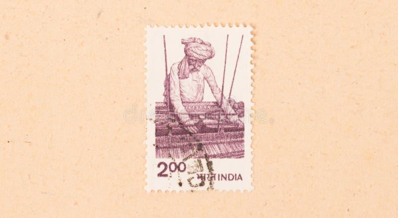 Un timbre imprimé en Inde montre un homme travaillant un métier à tisser, vers 1970 images libres de droits