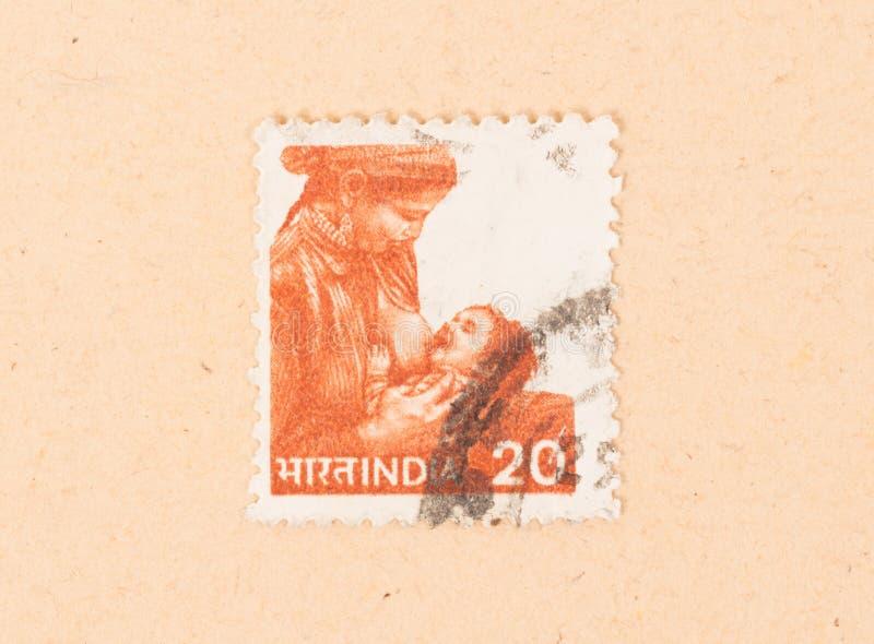Un timbre imprimé en Inde montre une femme allaitant un enfant, vers 1970 image libre de droits