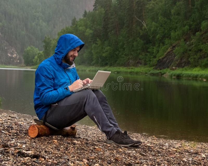 Un tipo barbuto contento in una giacca blu con un cappuccio si siede sulla banca di un fiume nella pioggia con un computer portat fotografia stock