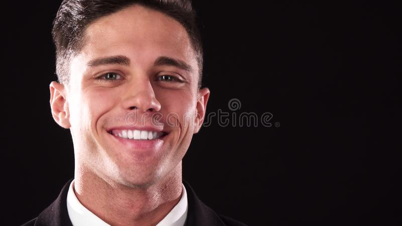 Un tipo bello sembra pensieroso e poi sorride nella macchina fotografica immagine stock