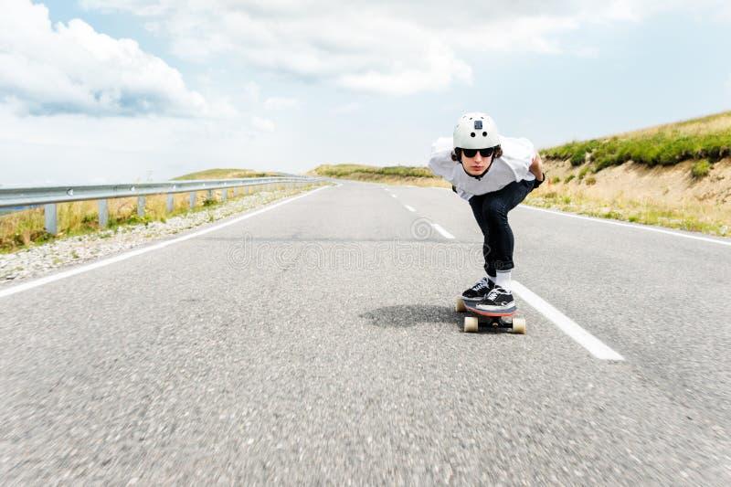 Un tipo che indossa un casco e gli occhiali da sole sta guidando il suo longboard su una strada campestre immagini stock
