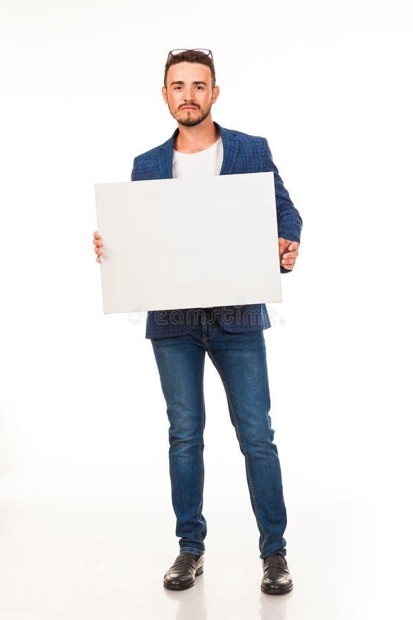Un tipo con una barba che posa con un segno bianco Possono essere usati per la pubblicità, il logo ed i biglietti da visita, i te immagini stock libere da diritti
