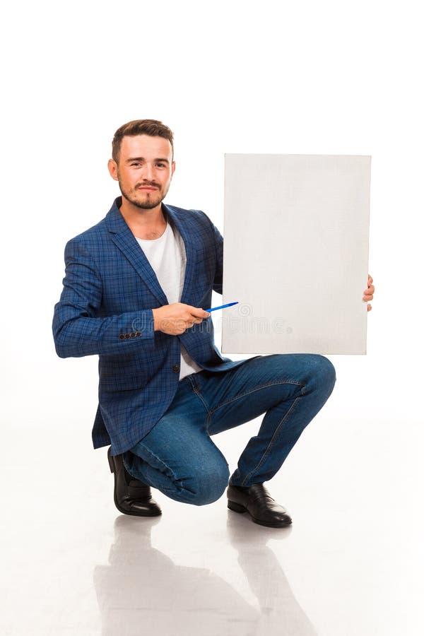 Un tipo con una barba che posa con un segno bianco Possono essere usati per la pubblicità, il logo ed i biglietti da visita, i te immagine stock libera da diritti