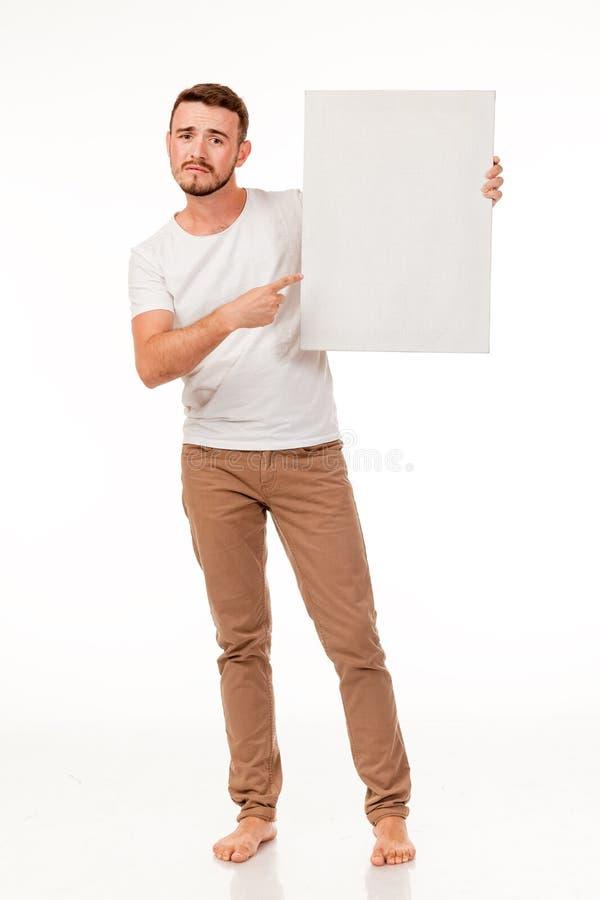 Un tipo con una barba che posa con un segno bianco Possono essere usati per la pubblicità, il logo ed i biglietti da visita, i te fotografia stock