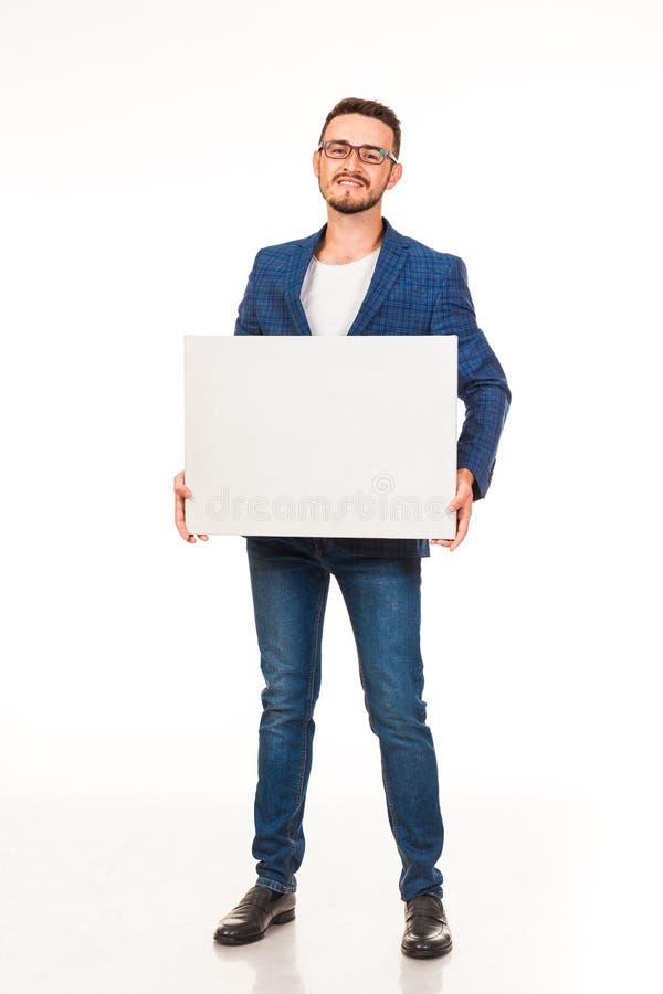 Un tipo con una barba che posa con un segno bianco Possono essere usati per la pubblicità, il logo ed i biglietti da visita, i te fotografia stock libera da diritti