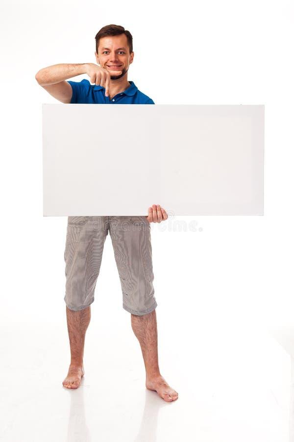Un tipo con una barba che posa con un segno bianco Può essere usato per disporre la pubblicità, il logo ed altro Vestito in una m fotografia stock
