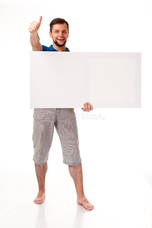 Un tipo con una barba che posa con un segno bianco Può essere usato per disporre la pubblicità, il logo ed altro Vestito in una m immagine stock libera da diritti