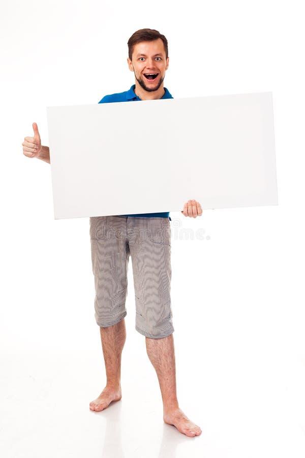 Un tipo con una barba che posa con un segno bianco Può essere usato per disporre la pubblicità, il logo ed altro Vestito in una m fotografie stock