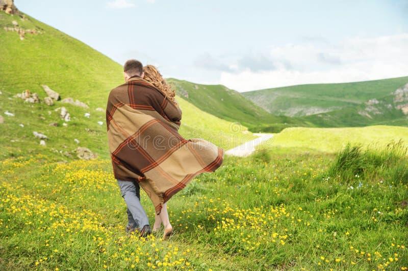 Un tipo con una ragazza avvolta in una passeggiata del plaid lungo una strada campestre fotografia stock libera da diritti