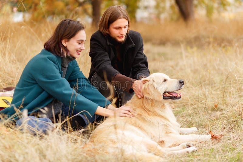 Un tipo con una ragazza che segna un documentalista nella radura di autunno fotografia stock