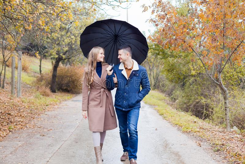 Un tipo con una ragazza va sotto la pioggia dell'ombrello fotografia stock libera da diritti