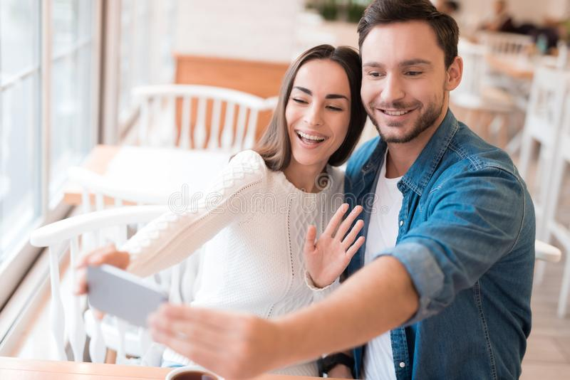 Un tipo e una ragazza fanno il selfie ad un caffè fotografie stock libere da diritti