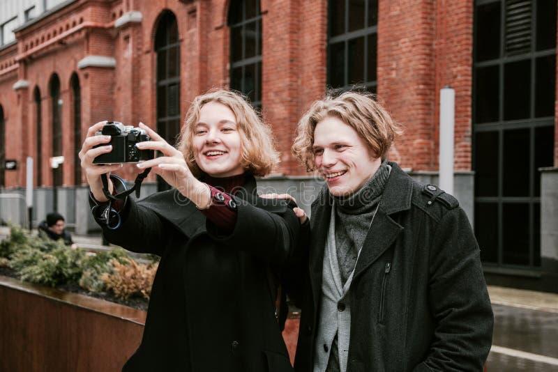 Un tipo e una ragazza prendere le immagini se stessi e fare i fronti divertenti fotografia stock