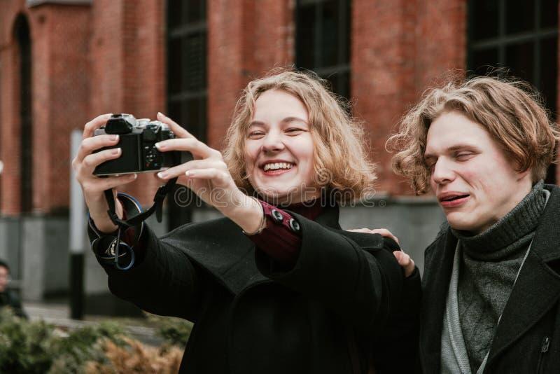 Un tipo e una ragazza prendere le immagini se stessi e fare i fronti divertenti immagine stock libera da diritti