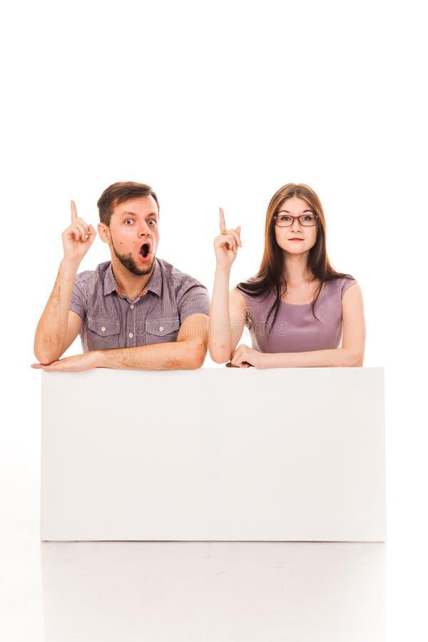 Un tipo e una ragazza stanno posando con un segno bianco, il cartone, un segno in loro mani immagini stock libere da diritti
