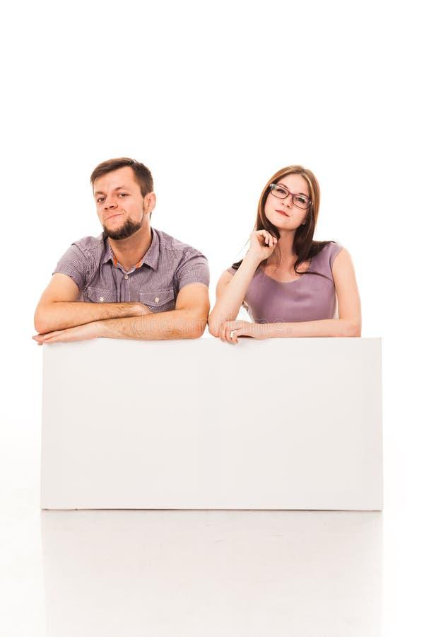 Un tipo e una ragazza stanno posando con un segno bianco, il cartone, un segno in loro mani immagine stock libera da diritti
