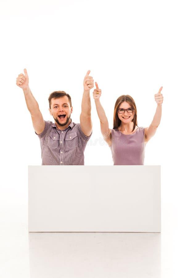 Un tipo e una ragazza stanno posando con un segno bianco, il cartone, un segno in loro mani fotografia stock libera da diritti