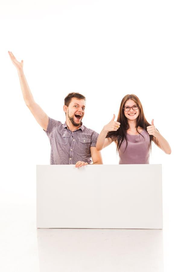 Un tipo e una ragazza stanno posando con un segno bianco, il cartone, un segno in loro mani immagine stock