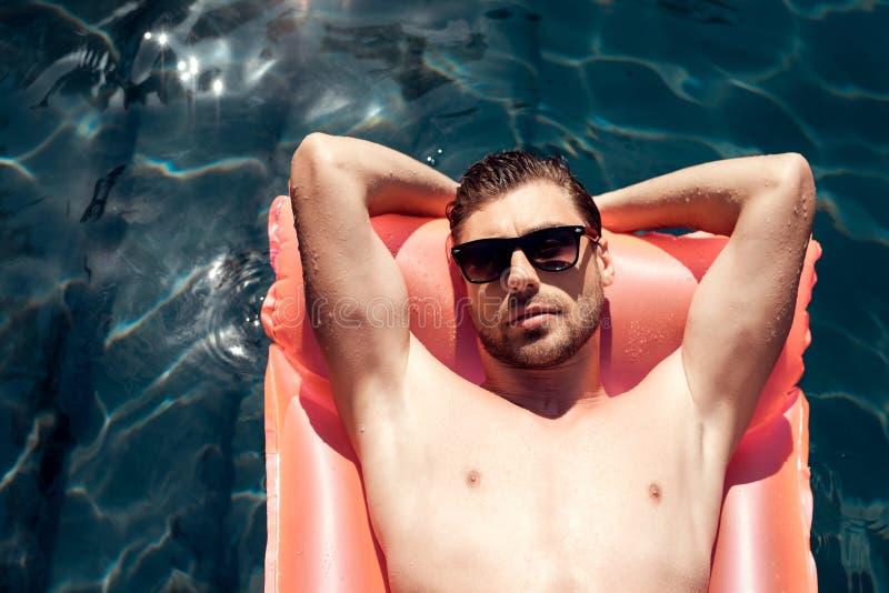 Un tipo in occhiali da sole sta galleggiando su un materasso gonfiabile nello stagno fotografia stock