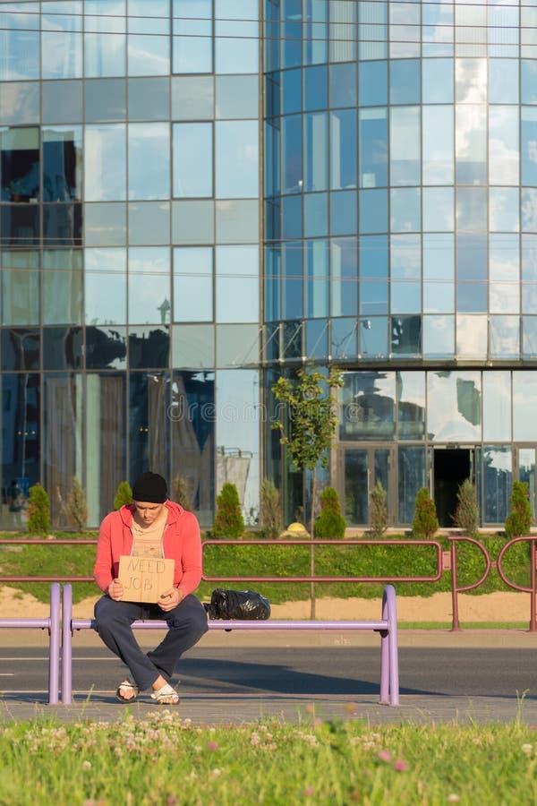 Un tipo senza tetto si siede sul banco con un cartone e un'iscrizione: lavoro di bisogno Nei precedenti è un centro di affari fotografia stock libera da diritti