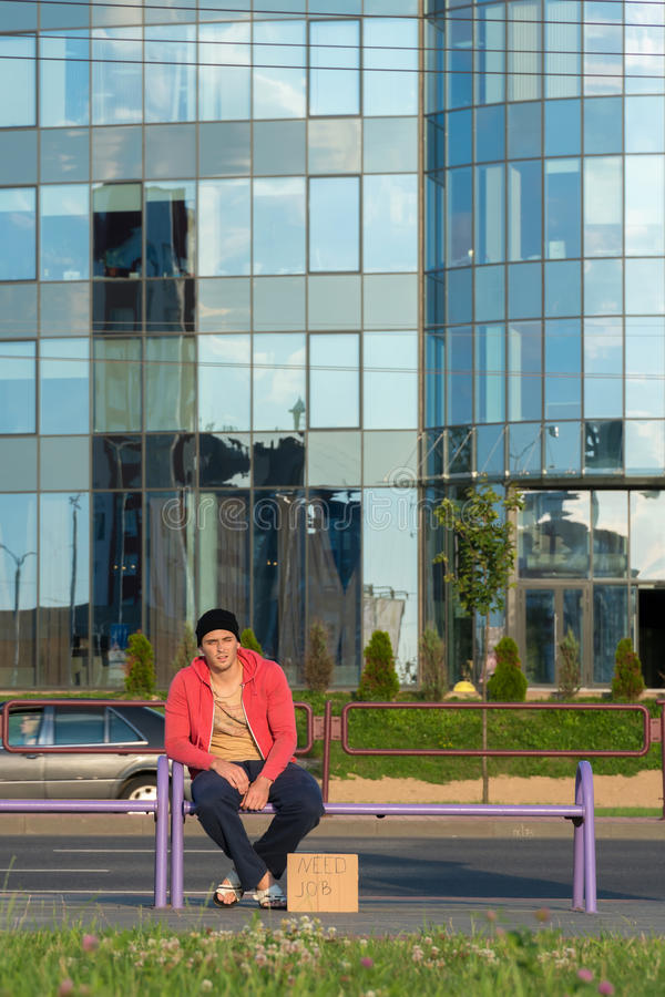 Un tipo senza tetto si siede sul banco con un cartone e un'iscrizione: lavoro di bisogno Nei precedenti è un centro di affari fotografie stock libere da diritti