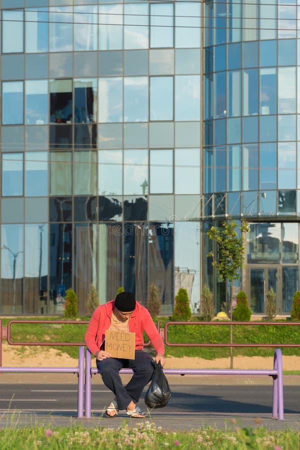 Un tipo senza tetto si siede sul banco con un cartone e un'iscrizione: soldi di bisogno Nei precedenti è un centro di affari fotografie stock