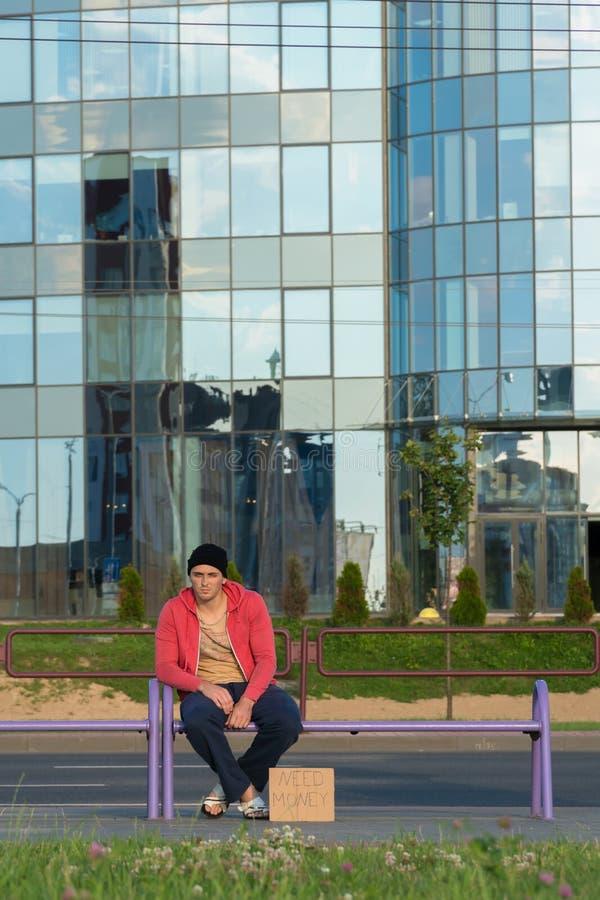 Un tipo senza tetto si siede sul banco con un cartone e un'iscrizione: soldi di bisogno Nei precedenti è un centro di affari fotografia stock libera da diritti