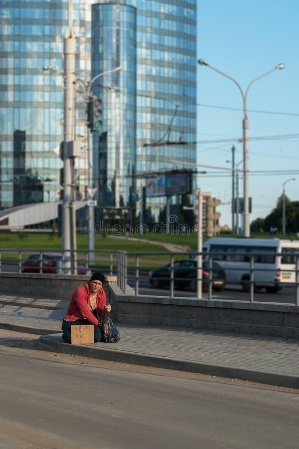 Un tipo senza tetto si siede sul marciapiede con un cartone e un'iscrizione: lavoro di bisogno Nei precedenti è un centro di affa immagini stock libere da diritti