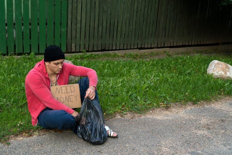 Un tipo senza tetto si siede sul marciapiede con un cartone e un'iscrizione: soldi di bisogno immagini stock
