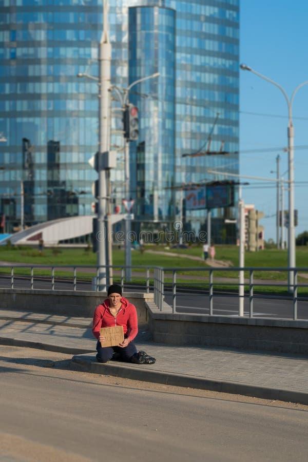 Un tipo senza tetto si siede sul marciapiede con un cartone e un'iscrizione: soldi di bisogno Nei precedenti è un centro di affar immagine stock