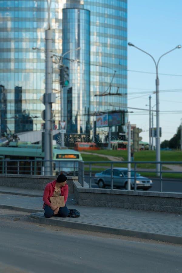 Un tipo senza tetto si siede sul marciapiede con un cartone e un'iscrizione: soldi di bisogno Nei precedenti è un centro di affar fotografia stock libera da diritti