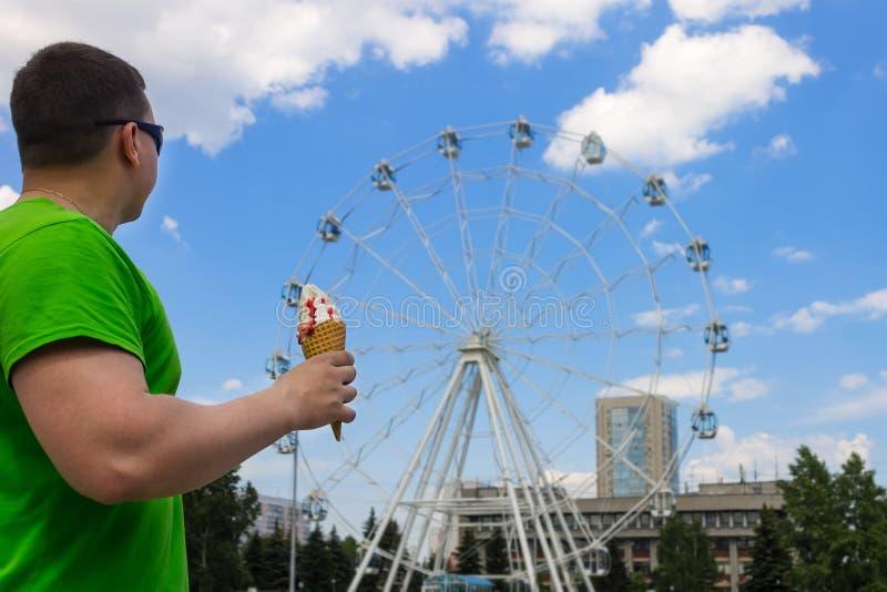 Un tipo in vestiti verdi mangia il gelato in un parco ed esamina una ruota di ferris fotografia stock libera da diritti