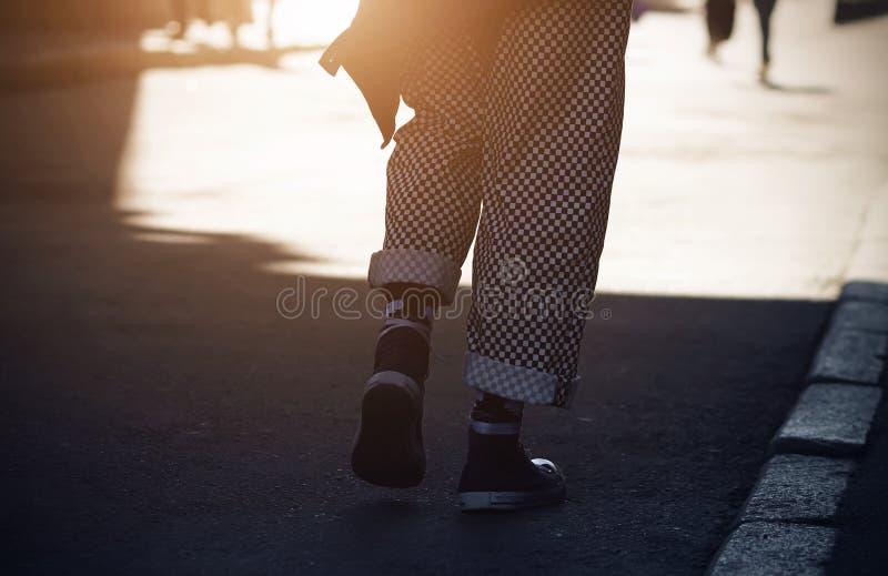 Un tipo, vestito in pantaloni di plaid e scarpe da tennis, passeggiate dall'ombra alla luce immagine stock