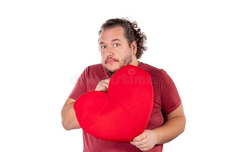 Un tir de studio d'un gros homme jugeant un oreiller en forme de coeur rouge d'isolement sur le fond blanc image libre de droits