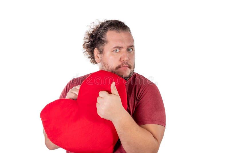 Un tir de studio d'un gros homme jugeant un oreiller en forme de coeur rouge d'isolement sur le fond blanc photographie stock